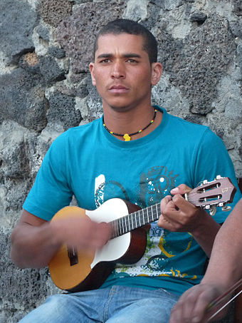 A young Cape Verdean man plays the Portuguese cavaquinho, a four-stringed instrument from which the `ukulele is descended. Cha das Caldeiras-Musicien.jpg