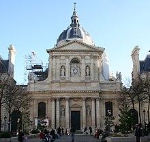 Chapelle en pierre blanche surmontée d'un toit en forme de coupole. Au-dessus de l'entrée se trouve une petite horloge blanche encadrée par deux statues faites de la même pierre que le bâtiment.