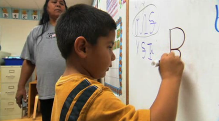 Oklahoma Cherokee language immersion school student writing in the Cherokee syllabary. Cherokeeclass.png
