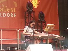 Seated woman playing a guzheng