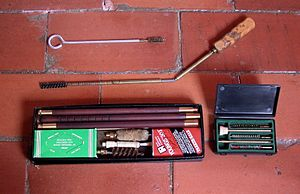 Firearm maintenance - An assortment of cleaning rods used for firearm maintenance: A short cleaning rod with a brass brush attached, a foldable cleaning rod with a nylon brush attached, a cleaning kit for a shotgun (note the thicker rod), and some different brushes.