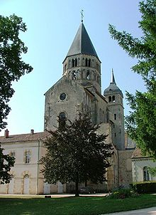 The remains of the Abbey of Cluny, a benedictine monastery. It is made of gray stone with several spires.