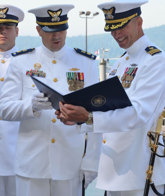 A Coast Guard chief warrant officer (CWO2, left) and an officer (commander, O-5, right) wearing Full Dress Whites Coast Guard dress white.png