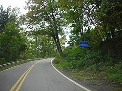 "A curvy, paved road flanked by green trees on both sides.  A sign on the right side of the road reads ""WELCOME TO PENNSYLVANIA."""