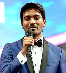 A picture of Dhanush with a Filmfare Award in his left hand as he looks at the camera and speaks.
