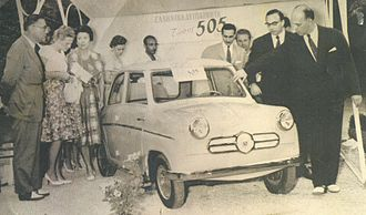 """Attica (automobiles) - Microcar Dimitriadis 505 (1958). The car is exhibited in a Trade Fair; Mr. Dimitriadis (to the right of the car, with glasses) and Greek minister for Industry, Mr. Nikolaos Martis (extreme right) can also be seen. Despite the """"interest"""", this venture received no state support."""