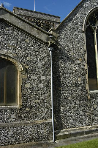 Kingsclere - Eastern end of St Mary's Church in October 2014, showing a gutter marked with the Orde-Powlett shield.