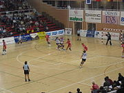 Handball player leaps towards the goal prior to throwing the ball, while the goalkeeper extends himself trying to stop it.