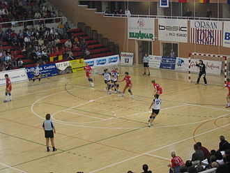 Handball - Handball player moves towards the goal prior to throwing the ball, while the goalkeeper waits to stop it.