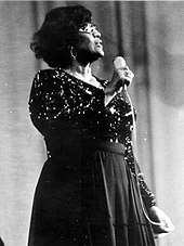 Black and white image of a woman wearing glasses and a dress with sequins, holding a microphone.