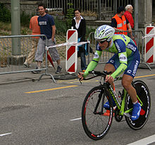 A cyclist riding a bicycle with a solid rear wheel and wearing a skin-tight lime green and blue jersey with white trim, with an aerodynamic helmet. Spectators watch him from the roadside.
