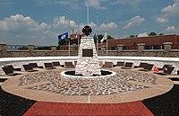 Kruhové náměstí s plastikou kříže ve středu a plaketami na vnější straně