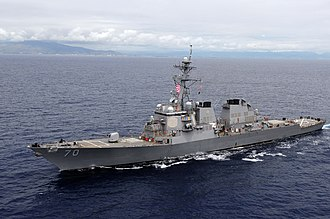 USS Hopper - A grey ship at sea with land in the background