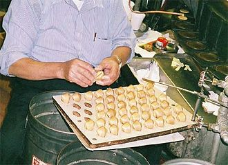 Fortune cookie - Hot fortune cookies being folded around paper fortunes