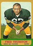 "A color photo of Fuzzy Thurston crouching down looking towards the camera. The text ""Fred Thurston, Green Bay Packers, Guard"" is printed below the photo."