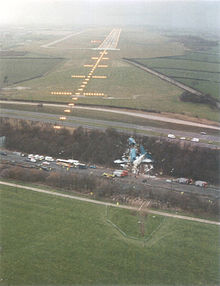 The wreck of an airliner lies between roads roughly 100m to the right of approach lights and several hundred metres in front of a runway. The wreck is broken into three large pieces, a nose section, a central section and a tail section. The tail section is turned around, the horizontal stabilizers resting in front of the wings of the central section.