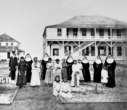 Marianne Cope and other Sisters of St Francis with the daughters of leper patients, at the Kaka`ako Branch Hospital, Hawaii. The Catholic Church established many of the world's modern hospitals. Gibson and Mother Marianne Cope.jpg