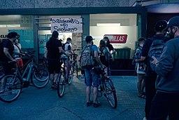 [Foto: Streik vor dem Lager von Gorrillas in Berlin im Jahr 2021; diverse Menschen auf Fahrrädern vor einem Ladenlokal in der Dämmerung]