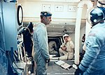 Guenter Wendt, seated at the Command Module hatch, signals to the crew.jpg
