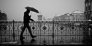 Guy with an umbrella battling rain and snow on a bridge.jpg