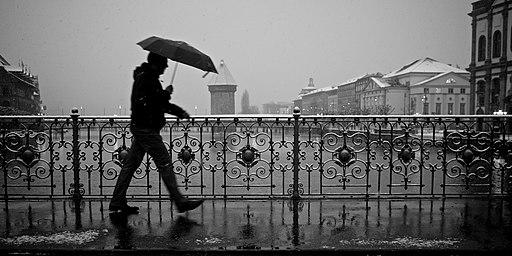 Guy with an umbrella battling rain and snow on a bridge