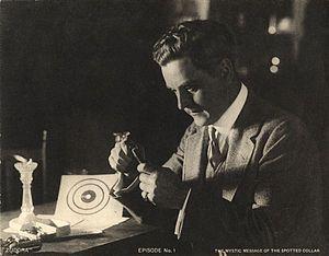 Harry Benham - Harry Benham loads bullets into a pistol magazine in a scene still for the 1914 Thanhouser silent film serial Zudora.