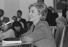 Photograph of Clinton making a presentation sitting at a table in front of a microphone