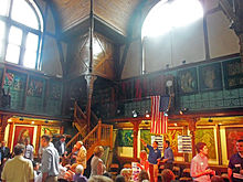 A large space with a wooden gallery along the upper portion, large windows above, and paintings and ornate decorations in the wooden walls. On the lower level, at the bottom of the image, there are a lot of people doing various things