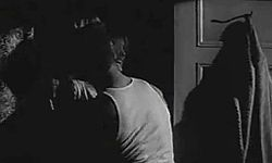 Man in sleeveless undershirt presses a woman against a wall in a dark room