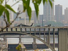 emergency landing of a helicopter on the 10th Avenue bridge seen from the bank amid green foliage
