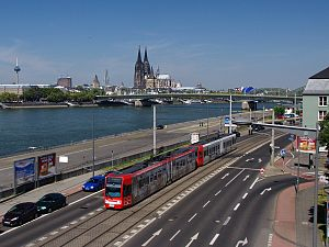 Cologne Stadtbahn - Light rail trainset in front of the river Rhine and Cologne Cathedral