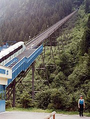 The white funicular train is waiting at the valley station. It enters the tunnel where the fire occurred after the short open-air section on the trestles. The tunnel entrance is visible.