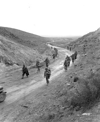 Battle of Kasserine Pass - Men of the 2nd Battalion, 16th Infantry Regiment of the U.S. 1st Infantry Division march through the Kasserine Pass and on to Kasserine and Farriana, Tunisia February 26, 1943.
