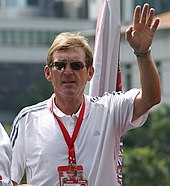 Kenny Dalglish in a white shirt, wearing sunglasses.