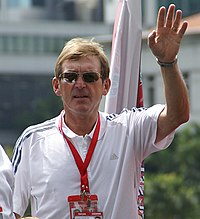 Colour photograph of Dalglish in Singapore, 2009. He is dressed casually, wearing sunglasses and has his hand raised