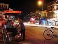 Lascar Two cycle-rickshaw drivers relaxing at night (4550339901).jpg