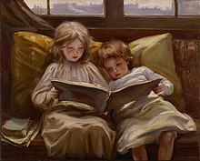Two young children sit together reading a book