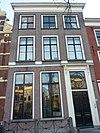 foto van Pand met bakstenen gevel met op verdieping teruggewerkte traveeën, afgedekt met rechte kroonlijst. Deuromlijsting. Hardstenen stoep met gesmeed ijzeren hek
