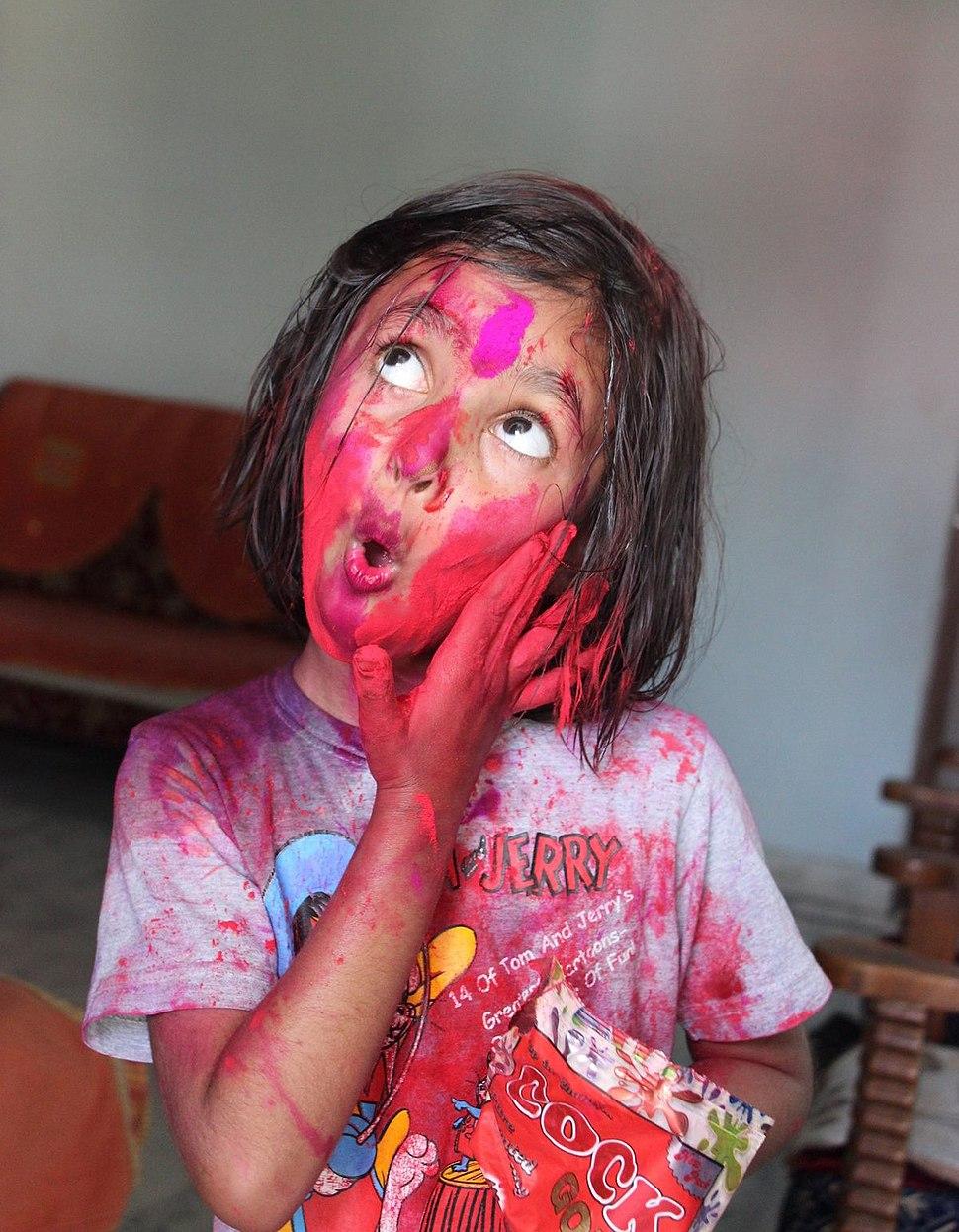 Little girl playing Holi with gulaal