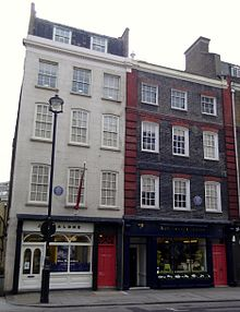 A color photograph of two adjacent buildings, the one on the left is white and the on the right is dark brown.
