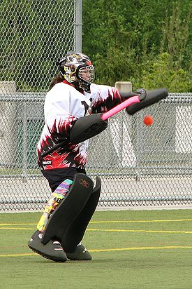 A goalkeeper makes a glove save. Equipment worn here is typical gear for a goalkeeper.