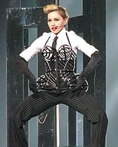 Madonna em um bustiê e terno elaborados, posando no palco