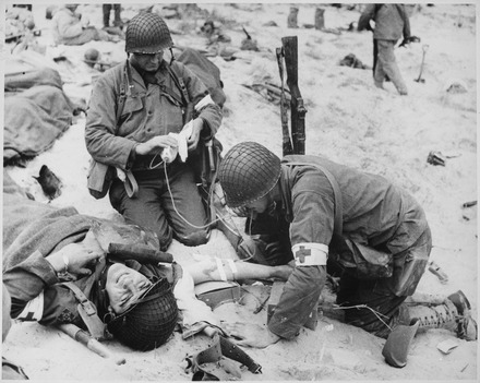 American medics helping injured soldier in France, 1944. Medics helping injured soldier in France, 1944 - NARA - 535973.tif