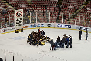 Michigan Wolverines men's ice hockey - Michigan posing with the Great Lakes Invitational banner after winning the 2015 GLI