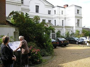 Moor Park, Farnham - Visitors on the public footpath through the grounds, reading the information panel at the front of the house