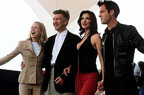 Les différents acteurs du film se tenant les uns à côté des autres devant un décor blanc du Festival de Cannes.