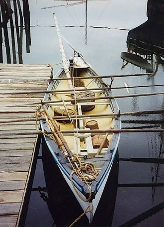 Whaleboat - A modern copy of a traditional whaleboat on display at Mystic Seaport. Another whaleboat, on the davits of a larger ship, is reflected in the water.