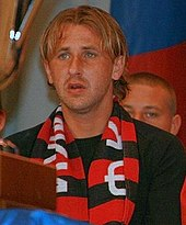 A white blond male seating on a stand with a black and red FC Khimki scarf around his neck.