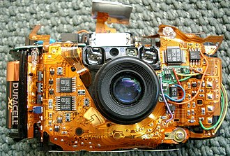 Flexible electronics - An Olympus Stylus camera without the case, showing the flex circuit assembly.