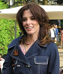 A smiling brown-haired woman wearing a blue denim jacket standing outside.